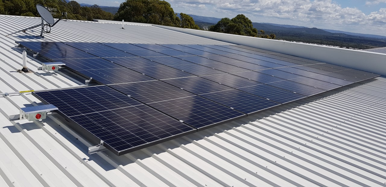 Sunrise over green shed roof with solar panels